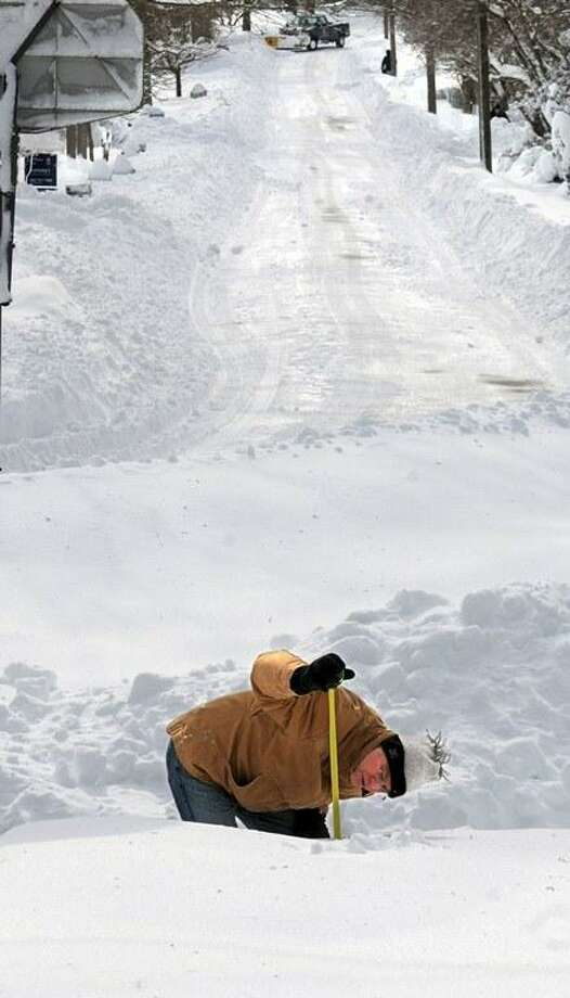 """The Blizzard of 2013, Nemo, in the Ivoryton section of Essex. Chet Arnold takes a break from shoveling to measure the snow. He got readings between 24"""" and 26"""". Mara Lavitt/New Haven Register 2/9/13"""