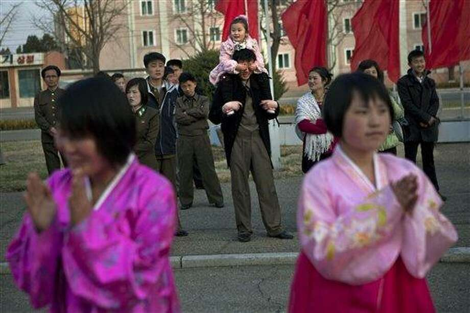 A North Korean child covers the eyes of her father as she sits on his shoulders watching mass folk dancing in front of Pyongyang Indoor Stadium in Pyongyang, North Korea, on Monday, April 15, 2013. Oblivious to international tensions over a possible North Korean missile launch, Pyongyang residents spilled into the streets Monday to celebrate a major national holiday, the birthday of their first leader, Kim Il Sung. (AP Photo/David Guttenfelder) Photo: ASSOCIATED PRESS / AP2013