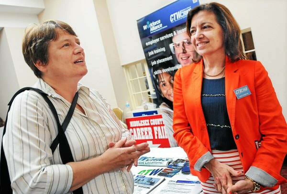 Catherine Avalone/The Middletown Press Middletown resident Ellen Ruth Delisio, a communications consultant with a degree in newspaper journalism from Syracuse talks to Ann Gawlak, of Middletown, a Business Services Specialist for Department of Labor CTWorks in Meriden about a grant writer position at the 2013 Spring Career Fair at the Crowne Plaza Tuesday afternoon. The annual event is sponsored by the Middlesex Chamber of Commerce.
