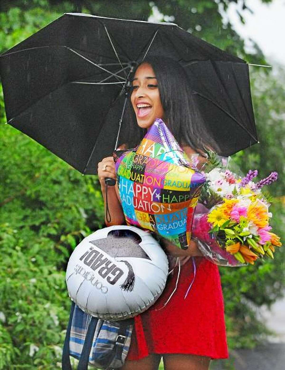 Catherine Avalone/The Middletown Press Soleybe Diaz, one of 82 graduates in the class of 2013 received balloons and bouqets of flowers from family members following graduation Tuesday evening at Portland High School. School administration decided Monday morning to move commencement indoors.