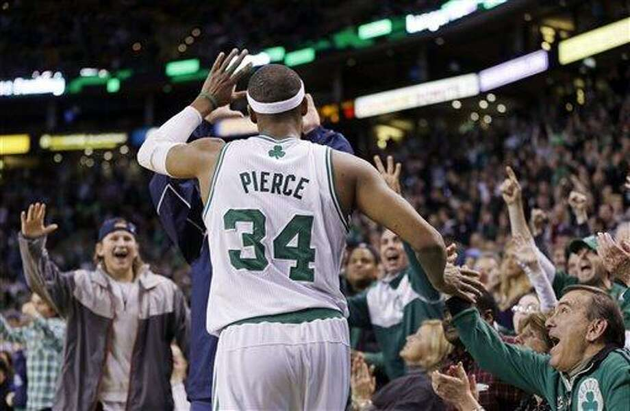Boston Celtics forward Paul Pierce (34) receives high-fives from courtside fans near the end of the second overtime in an NBA basketball game against the Denver Nuggets in Boston, Sunday, Feb. 10, 2013. The Celtics won 118-114 in triple-overtime. (AP Photo/Elise Amendola) Photo: ASSOCIATED PRESS / AP2013