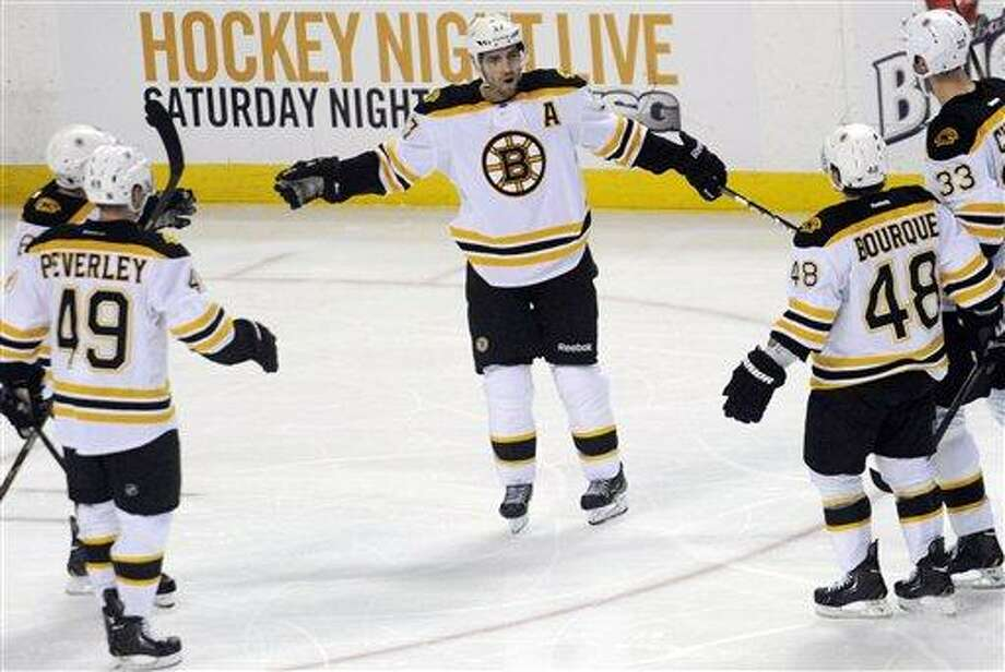 Boston Bruins center Patrice Bergeron (center) celebrates his third period goal Buffalo Sabres' during an NHL hockey game in Buffalo, N.Y., Sunday, Feb. 10, 2013. Boston won, 3-1. (AP Photo/Gary Wiepert) Photo: ASSOCIATED PRESS / AP2013
