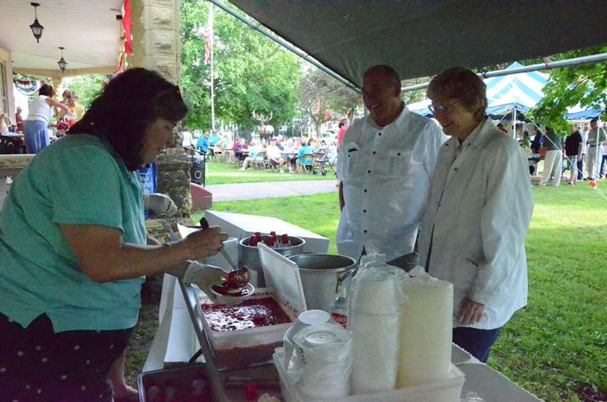 Leah McDonald/Oneida Daily Dispatch Phyllis Pryor serves strawberry treats to Steve Bender and Diane Myers at the Oneida Elks Club's annual Strawberry Festival Tuesday, June 18, 2013.