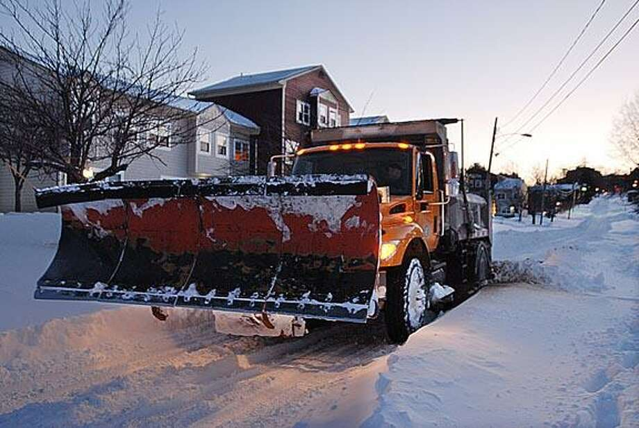 Andrew Phillip Avalone/Special to the Press  A city plow spins the wheels while stuck on William Street in Middletown.