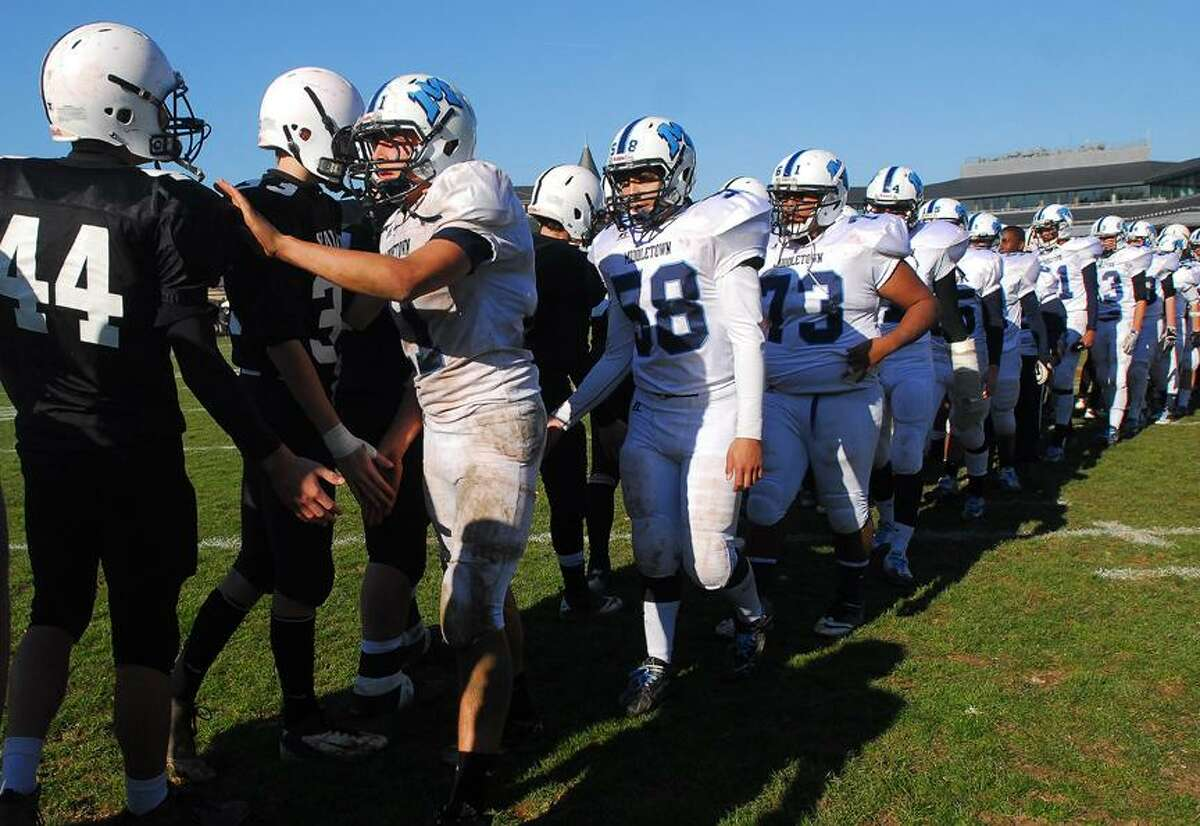 Catherine Avalone/The Middletown Press Players from Middletown High and Xavier shake hands in 2012 after what would be the last Thanksgiving Day game between the city opponents.