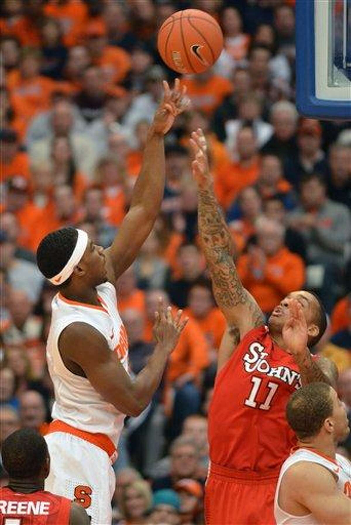 AP Photo Syracuse's C. J. Fair, left, shoots over St. John's D'Angelo Harrison during the first half of their game in Syracuse on Sunday.