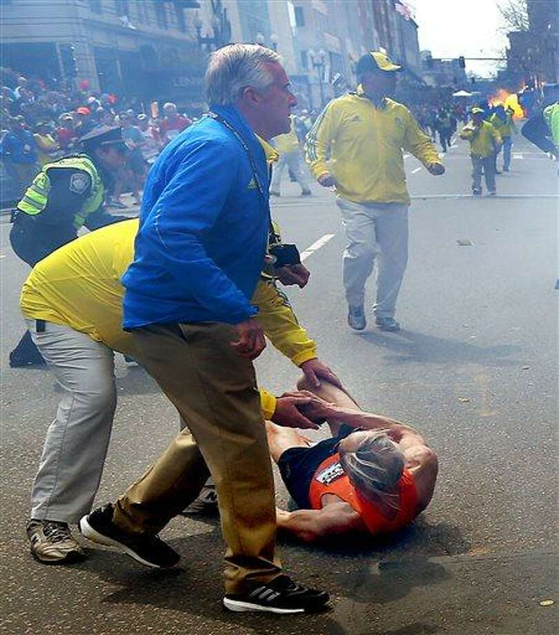 Bill Iffrig, 78, lies on the ground as police officers react to a second explosion at the finish line of the Boston Marathon in Boston, Monday, April 15, 2013. Iffrig, of Lake Stevens, Wash., was running his third Boston Marathon and near the finish line when he was knocked down by one of two bomb blasts. (AP Photo/The Boston Globe, John Tlumacki) Photo: AP / The Boston Globe