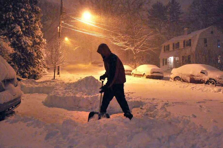 Charles Melita shovels snow along Hemlock Road in New Haven as the storm ramped up Friday in the early evening. Peter Casolino/Register