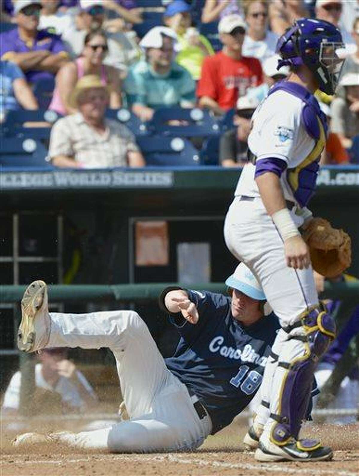 North Carolina's Colin Moran (18) slides in at home plate to score on an RBI single by Skye Bolt as LSU catcher Ty Ross looks on during the seventh inning of an NCAA College World Series elimination baseball game in Omaha, Neb., Tuesday, June 18, 2013. (AP Photo/Ted Kirk)