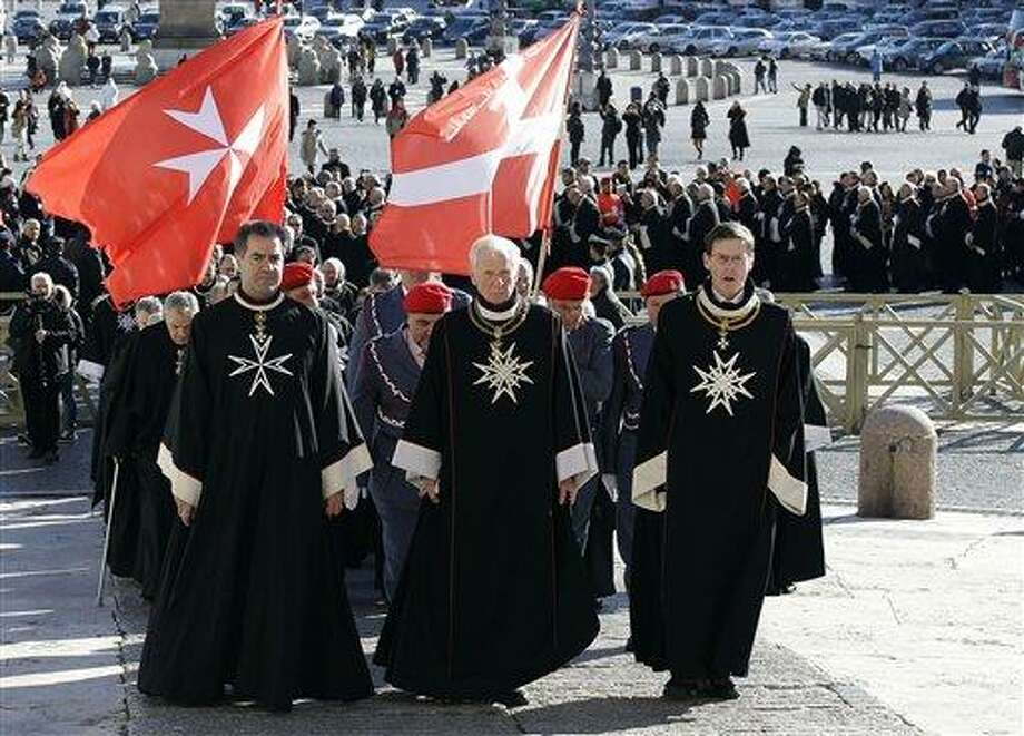 Members of the Knights of Malta walk in procession towards St. Peter's Basilica during a celebration to mark the 900th anniversary of the Order of the Knights of Malta, at the Vatican, Saturday, Feb. 9, 2013. The order traces its history to the 11th century with the establishment of an infirmary in Jerusalem that cared for people of all faiths making pilgrimages to the Holy Land. It is the last of the great lay chivalrous military orders like the Knights Templars that combined religious fervor with fierce military might to protect and expand Christendom from Islam's advance during the Crusades. In February 1113, Pope Paschal II issued a papal bull recognizing the order as independent from bishops or secular authorities, reason for Saturday's anniversary celebrations at the Vatican. (AP Photo/Gregorio Borgia) Photo: AP / AP
