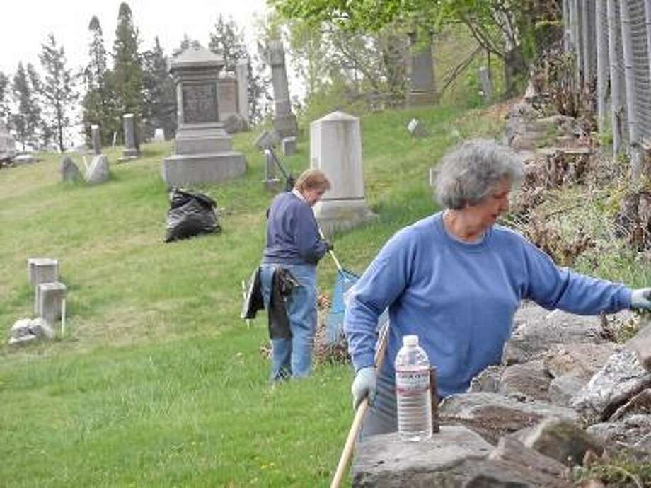 Torrington residents clean the grounds of a cemetery during a 2012 Earth Day cleanup. -- Register Citizen File Photo