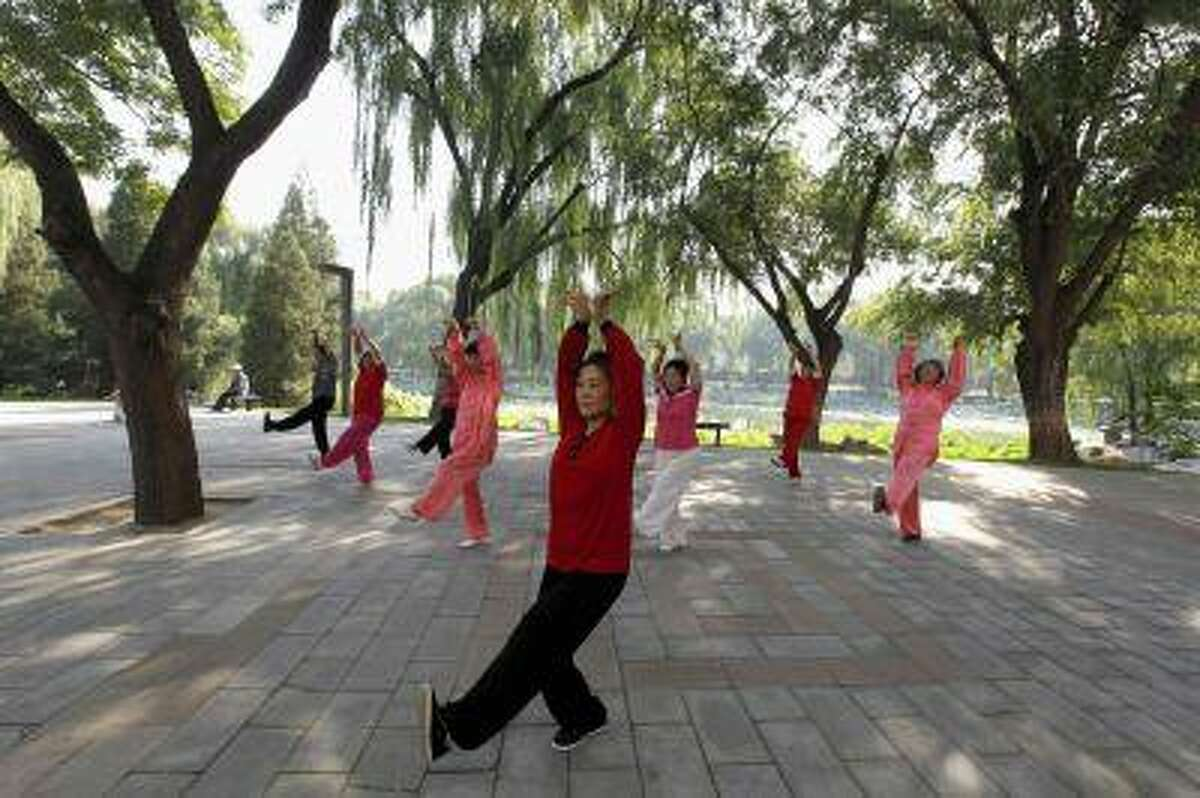 People practice tai chi, a Chinese martial art, during morning exercises at Longtan Park in Beijing in this Sept. 13, 2010 file photo. (REUTERS/Grace Liang/Files)