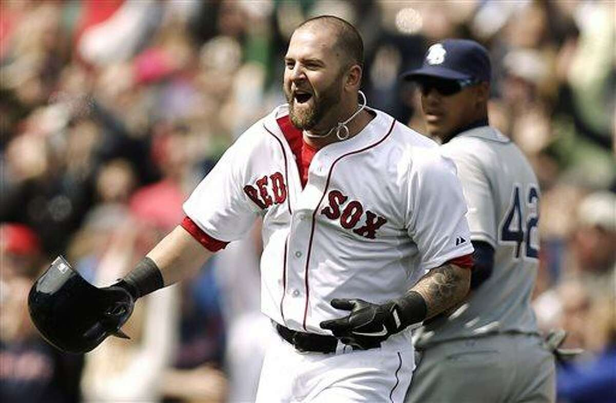 Boston Red Sox's Mike Napoli celebrates after his game-winning double as Tampa Bay Rays' Yunel Escobar watches during the ninth inning of a baseball game at Fenway Park in Boston on Monday, April 15, 2013. Boston won 3-2. (AP Photo/Winslow Townson)