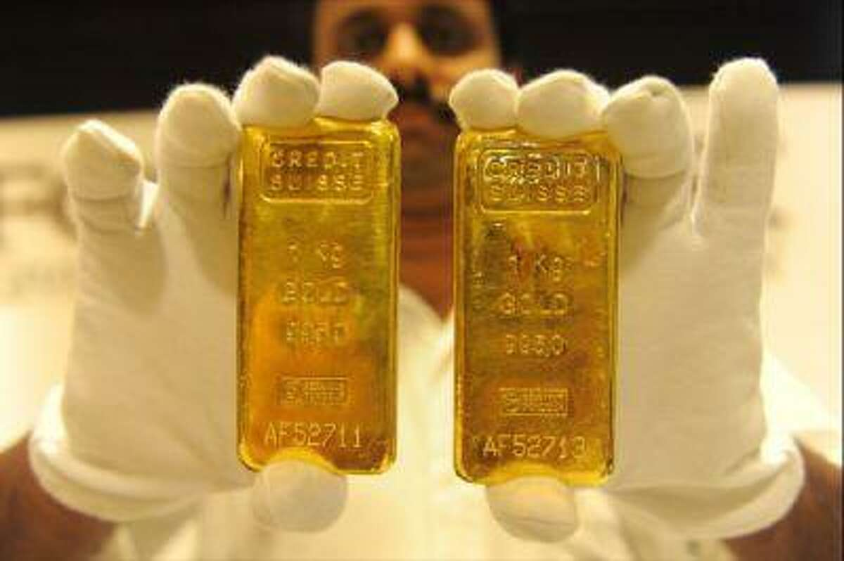 A jewellery shop employee displays 24-carat gold bars in Ahmedabad on August 20, 2011.
