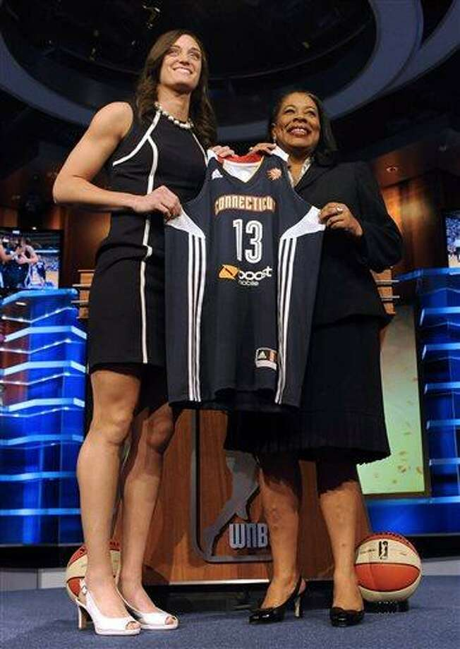Connecticut's Kelly Faris holds up a Connecticut Sun jersey with WNBA president Laurel J. Richie after Connecticut selected Faris as the No. 11 pick in the WNBA basketball draft in Bristol, Conn., Monday, April 15, 2013. (AP Photo/Jessica Hill) Photo: AP / FR125654 AP