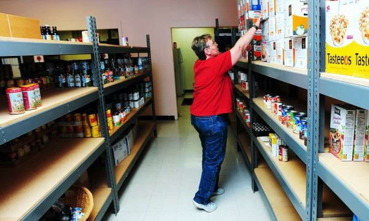 Sandy Hogan, pantry manager, places a box of matzo on a shelf at the Jewish Family Service food pantry on Whalley Avenue in New Haven earlier this month. Arnold Gold/Register