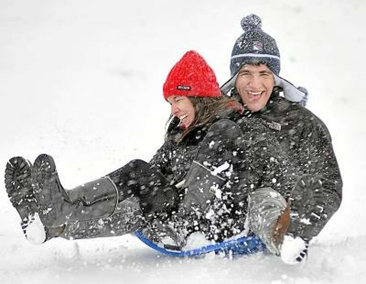 Catherine Avalone/The Middletown Press Wesleyan student Mike Glasser, of New York and his friend from back home, Jessica Russo sled down Foss Hill at Wesleyan University Friday afternoon during the blizzard.