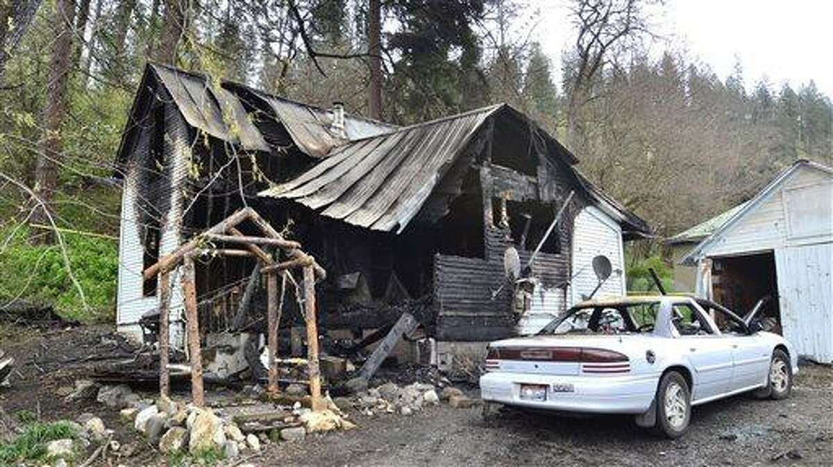 This photo shows the charred remains of a house on Cedar Avenue, Saturday, April 13, 2013 in Orofino, Idaho. An extension cord hooked to an electric grill on a porch shorted out and started a house fire that killed five people Saturday morning, a northern Idaho fire official says. ((AP Photo/Lewiston Tribune, Steve Hanks)