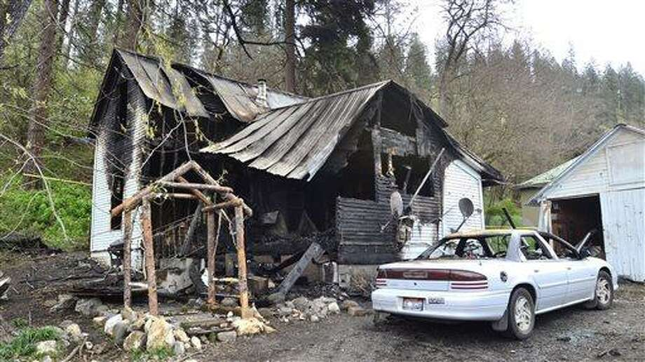 This photo shows the charred remains of a house on Cedar Avenue, Saturday, April 13, 2013 in Orofino, Idaho. An extension cord hooked to an electric grill on a porch shorted out and started a house fire that killed five people Saturday morning, a northern Idaho fire official says. ((AP Photo/Lewiston Tribune, Steve Hanks) Photo: AP / Lewiston Tribune