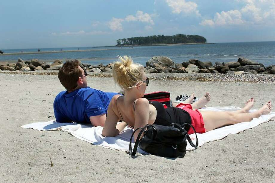 Matt Sioverio and Allie Bendzinski laying by the water at Silver Sands Beach in Milford. Nicole Dellolio/ For the Register