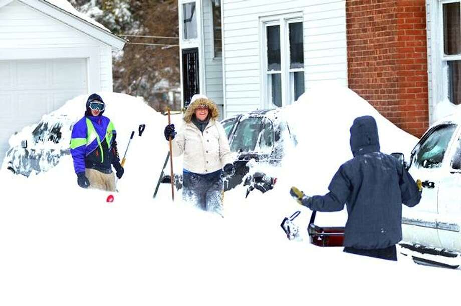 Catherine Avalone/The Middletown Press Middletown residents, Scott Sypek, (left to right) and his wife, Karla Sypek and brother, Kris Sypek dig out from the blizzard Saturday morning.