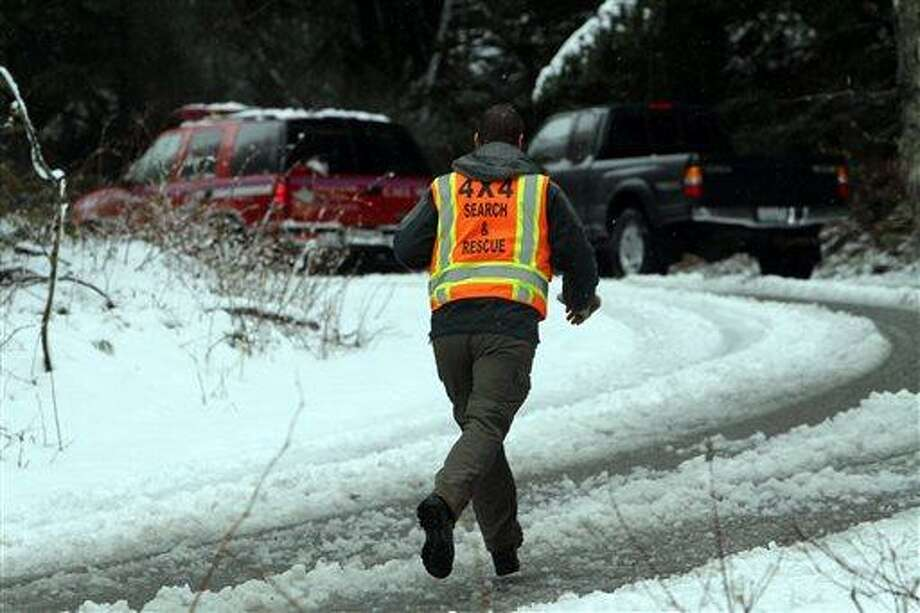 A man with King County Search and Rescue runs toward scene of avalanche at exit 47 along I-90 near Snoqualmie Pass, Sat. April 13, 2013. (Photo by Ken Lambert/The Seattle Times) Photo: AP / The Seattle Times