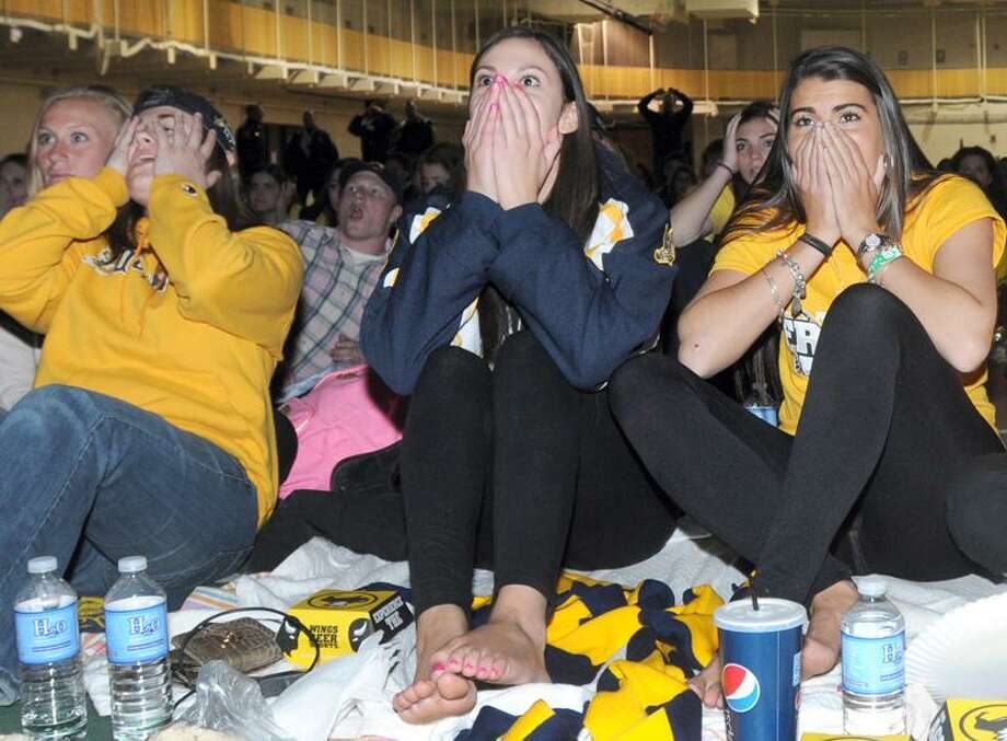 Quinnipiac University students (Left to right) Erin Morton Ashley Kopacki and Brittany Gentile react to a Yale score and the first goal of the game  during second period of the  Quinnipiac University and Yale University of the  Frozen Four NCAA Division 1 Hockey Championship Game as they watch the game with other students on a 16-foot x 9-foot  television screen Saturday evening April 13, 2013 at the Qunnipiac University Fitness and Recreation Center in Hamden.  Photo by Peter Hvizdak / New Haven Register Photo: New Haven Register / ©Peter Hvizdak /  New Haven Register