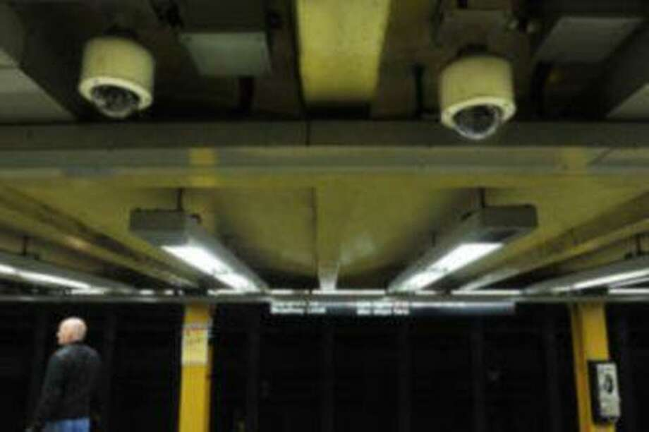 File- In this Tuesday, March 30, 2010, file photo, two ceiling-mounted video surveillance cameras are seen as a man awaits the arrival of a No. 1 subway train at the 34th Street station, in New York. (AP Photo/Stephen Chernin) Photo: AP / FR76594 AP net