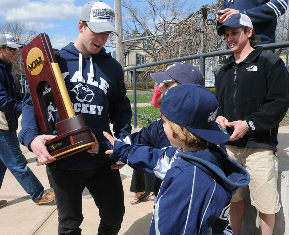 """The NCAA men's national hockey champions, Yale University, returns home from the Frozen Four in Pittsburgh, where they beat crosstown rivals Quinnipiac Univeristy, 4-0. Tyler Cacace age 8 of East Haven and Eli Kane age 5 of Woodbridge reach to touch the trophy held by team captain Andrew Miller. Jess Kane of Woodbridge, right, coaches Mites hockey. Mara Lavitt/New Haven Register <a href=""""mailto:mlavitt@newhavenregister.com"""">mlavitt@newhavenregister.com</a>4/14/13"""