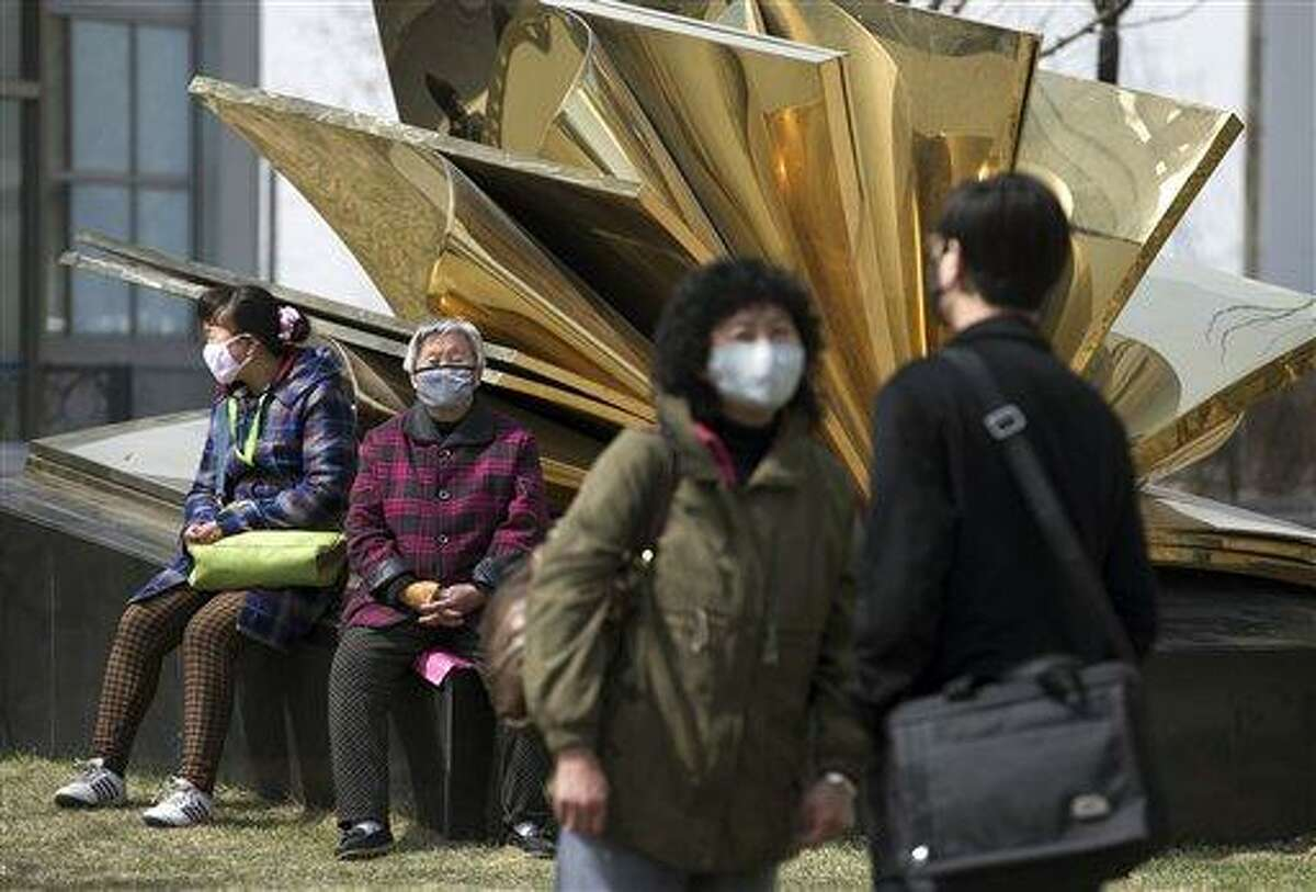 Chinese people wear face masks near a specialized fever clinic inside the Ditan Hospital, where a Chinese girl is being treated for the H7N9 strain of bird flu, in Beijing Sunday, April 14, 2013. A World Health Organization official said Sunday that it wasn't surprising that a new strain of bird flu has spread to China's capital after sickening dozens in the eastern part of the country. (AP Photo/Andy Wong)