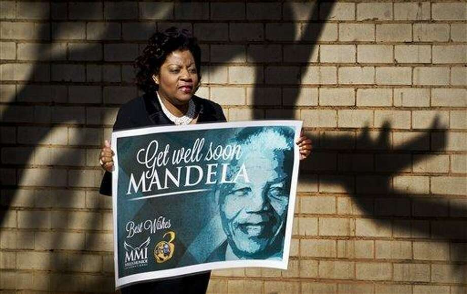 A wellwisher carrying get-well placard arrives at the Mediclinic Heart Hospital where former South African President Nelson Mandela is being treated in Pretoria, South Africa Sunday, June 16, 2013. South Africa's president says that Nelson Mandela is seeing sustained improvement from the recurring lung infection that is forcing him to spend a ninth day in the hospital. (AP Photo/Ben Curtis) Photo: AP / AP