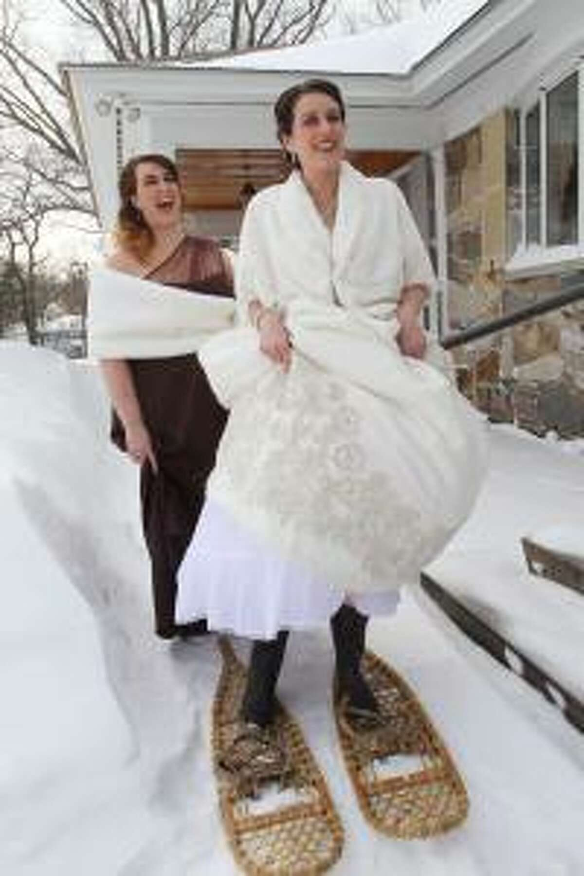 Bride Kathryn Jussaume of Lowell, with her sister and maid of honor Adrianne Richard of Lowell, left, poses in snowshoes as Adrianne's husband takes a photo in front of her parents' house in Lowell. They were headed to her wedding in North Andover, at the end of a blizzard which dropped two feet of snow in Massachusetts. (SUN/Julia Malakie)