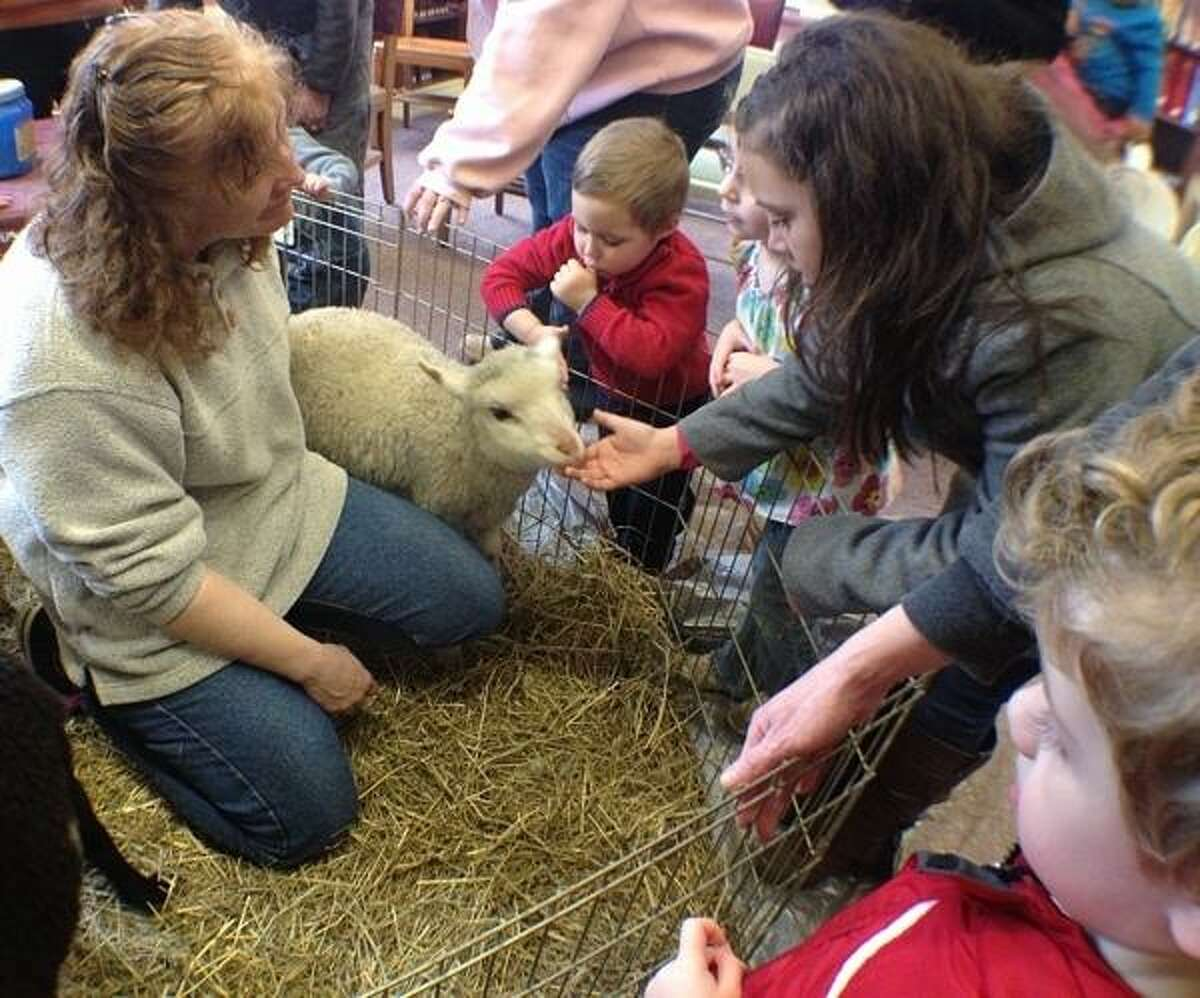 PHOTO BY JOHN HAEGER @ ONEIDAPHOTO ON TWITTER/ONEIDA DAILY DISPATCH Lisa Mawson talks about her sheep as children pet them during a program at the Oneida Public Library on Friday, April 12, 2013