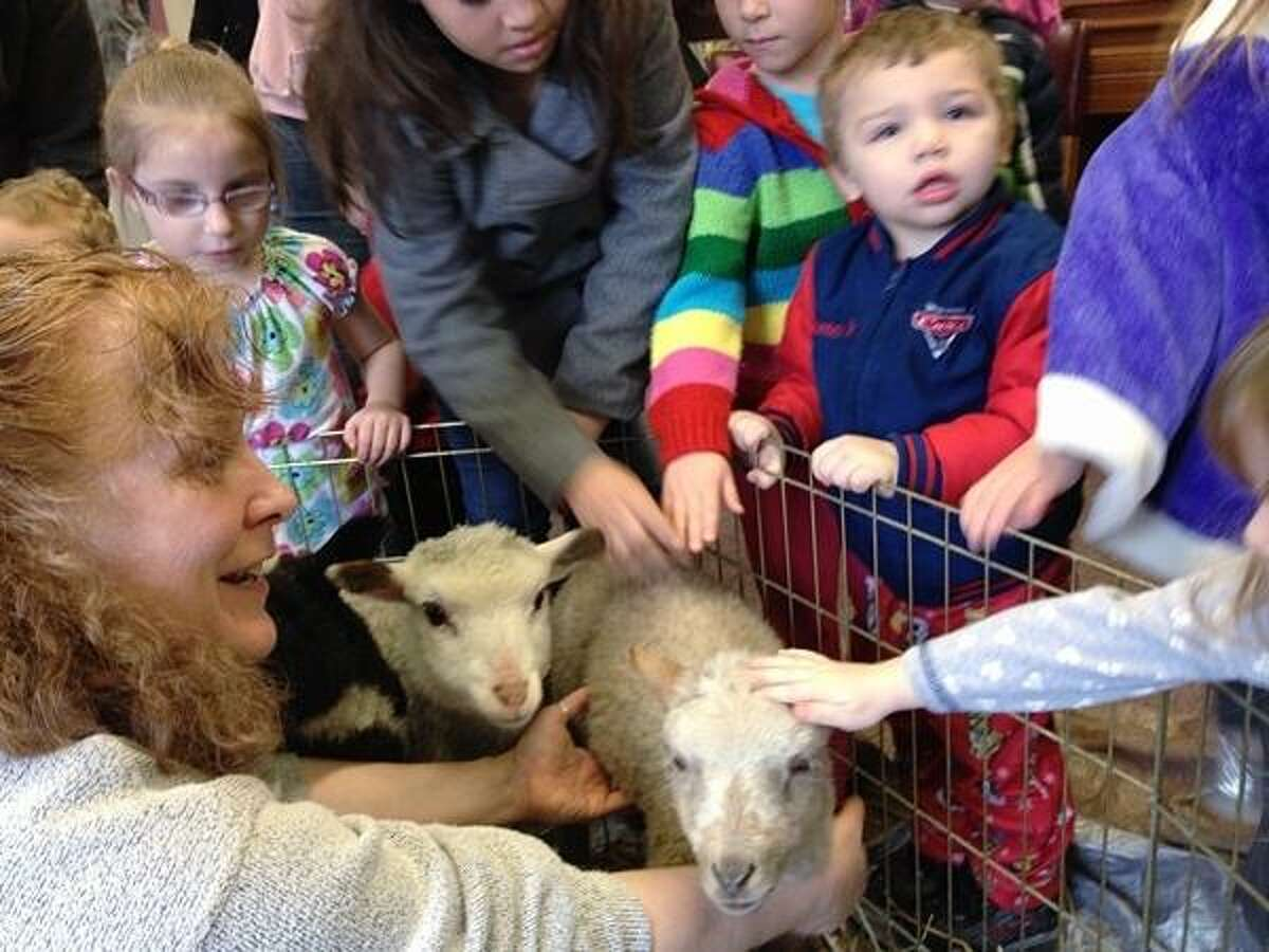 PHOTO BY JOHN HAEGER @ ONEIDAPHOTO ON TWITTER/ONEIDA DAILY DISPATCH Lisa Mawson talks about her sheep as children pet them during a program at the Oneida Public Library on Friday, April 12, 2013.