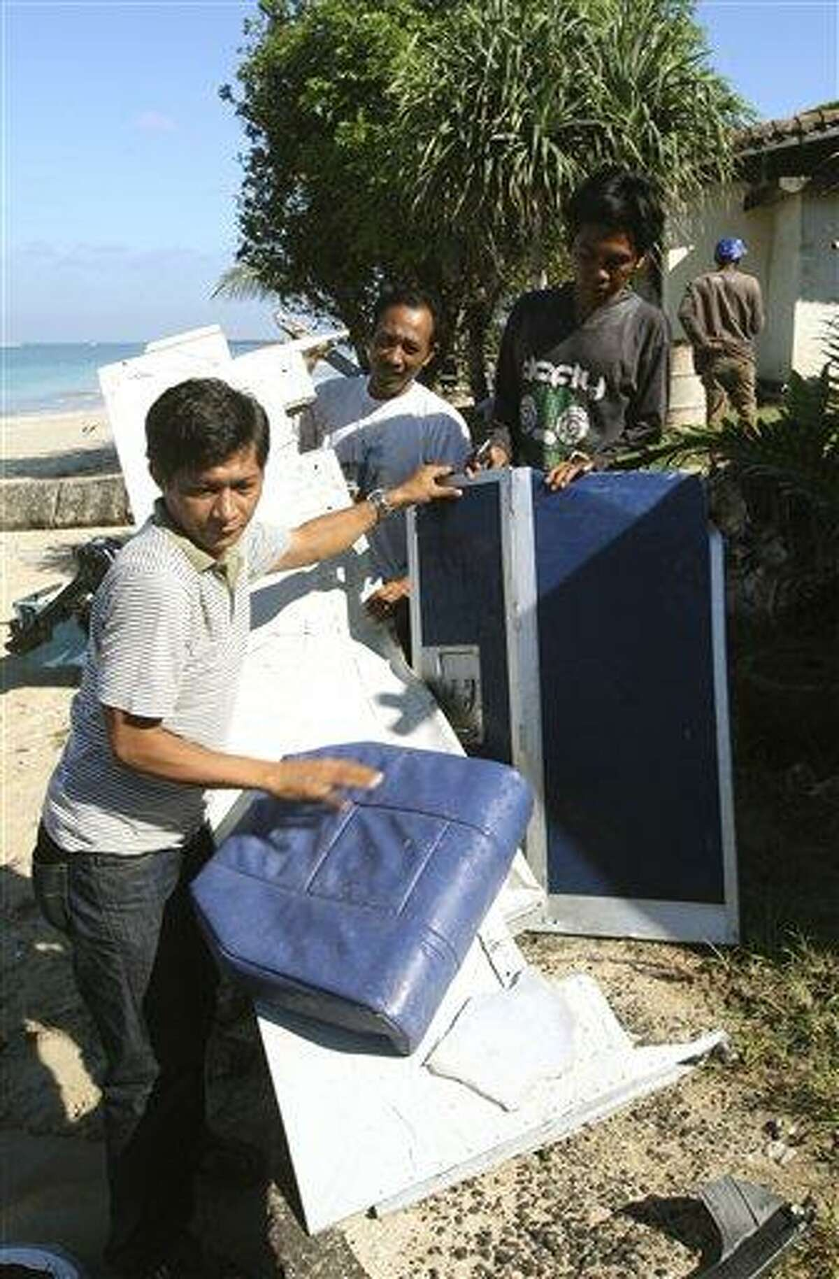 Indonesian men collect pieces of a Lion Air jet a day after the aircraft crashed into the ocean at Jimbaran beach, in Bali, Indonesia on Sunday, April 14, 2013. All 108 passengers and crew survived after the new Lion Air jet crashed into the ocean and snapped into two while attempting to land Saturday on the Indonesian resort island of Bali, injuring up to 45 people. (AP Photo/Firdia Lisnawati)