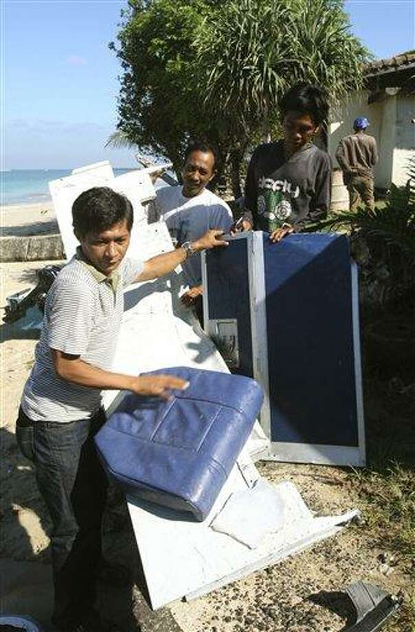 Indonesian men collect pieces of a Lion Air jet a day after the aircraft crashed into the ocean at Jimbaran beach, in Bali, Indonesia on Sunday, April 14, 2013.  All 108 passengers and crew survived after the new Lion Air jet crashed into the ocean and snapped into two while attempting to land Saturday on the Indonesian resort island of Bali, injuring up to 45 people. (AP Photo/Firdia Lisnawati) Photo: AP / AP