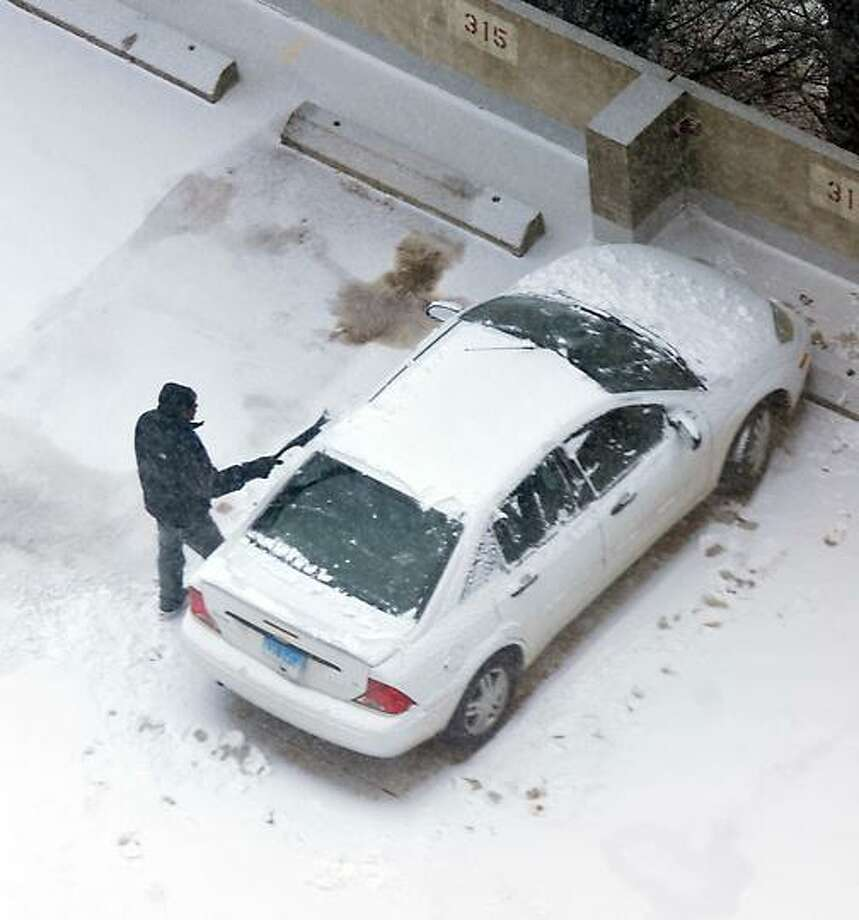 New Haven-- A man clears off his car at the Bella Vista senior housing complex as the snow begins to fall. Photo-Peter Casolino 2/8/13