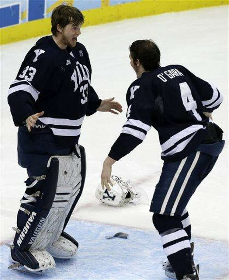 Yale goalie Jeff Malcolm (33) begins to celebrate with Rob O'Gara (4) after shutting out Quinnipiac 4-0 to win the NCAA men's college hockey Frozen Four national championship game in Pittsburgh, Saturday, April 13, 2013. (AP Photo/Gene Puskar) Photo: ASSOCIATED PRESS / AP2013