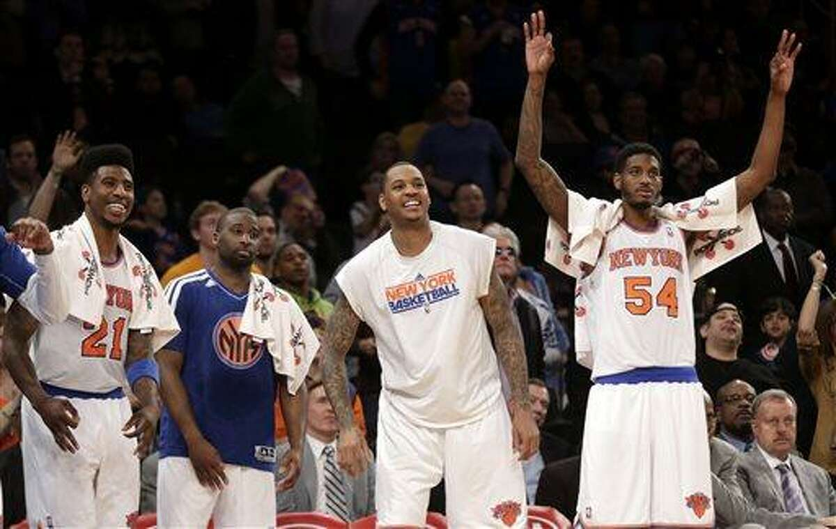 From left, New York Knicks' Iman Shumpert, Raymond Felton, Carmelo Anthony and Solomon Jones react as they watch the end of an NBA basketball game against the Indiana Pacers, Sunday, April 14, 2013, in New York. The Knicks won 90-80. (AP Photo/Seth Wenig)