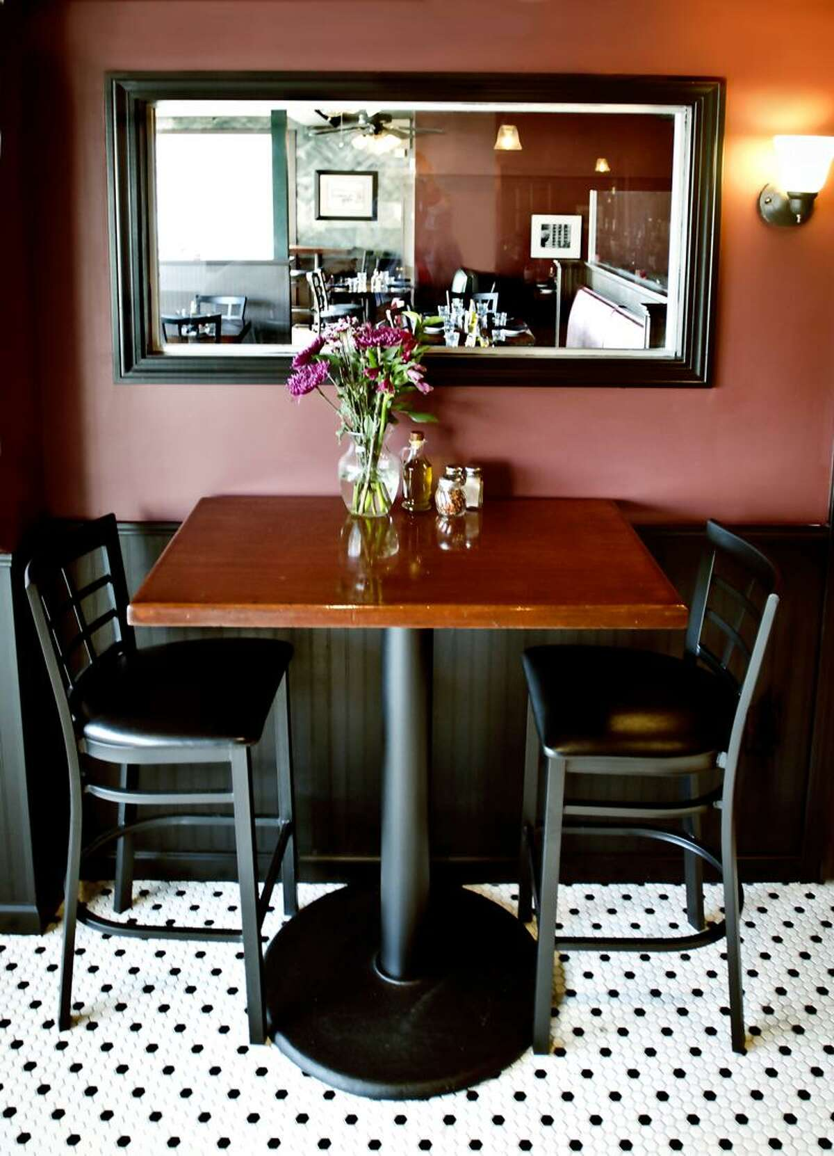 Hamden-Bistro table in the new bar at Cafe Amici. The restaurant is visible through the window at the table. Melanie Stengel/Register