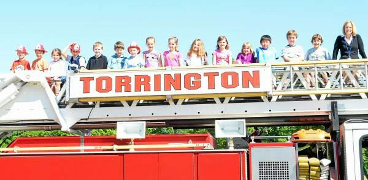 Kathleen Nilsson's First Grade class sits atop Ladder 2 Monday morning after Tristan Ladona, second from right, received a ride to school from Torrington Fire Department. (Jenny Golfin - The Register Citizen)