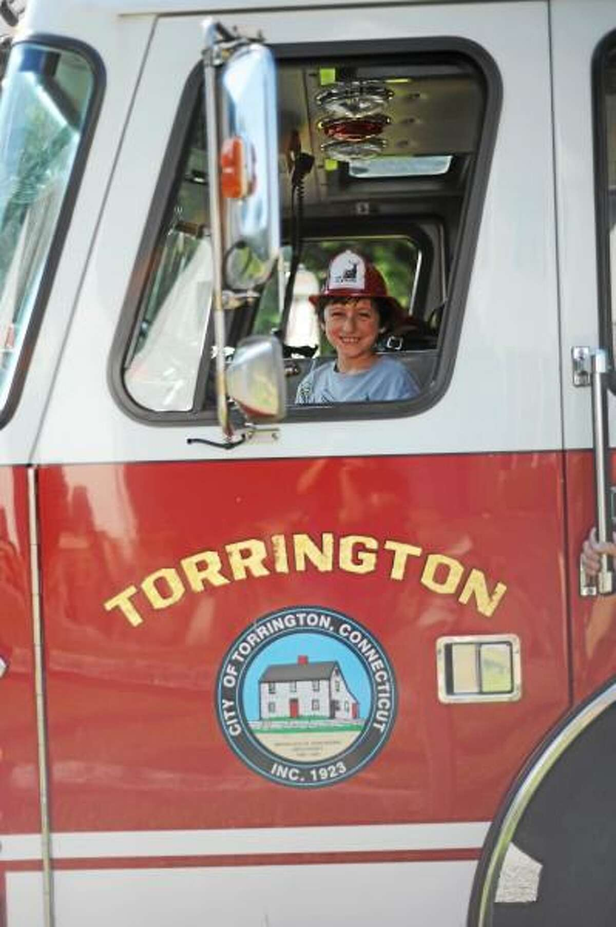 Tristan Ladonna sitting by the wheel of a Torrington Fire Truck. His parents were the winning bidders on a fire truck ride to school at the 2012 Toast to Technology P.T.O. fundrasier event. Ladonna opted to have his special ride to school on the second to last day of school. (Submitted photo courtesy of Rebakah Ladonna - Bekah Photography)