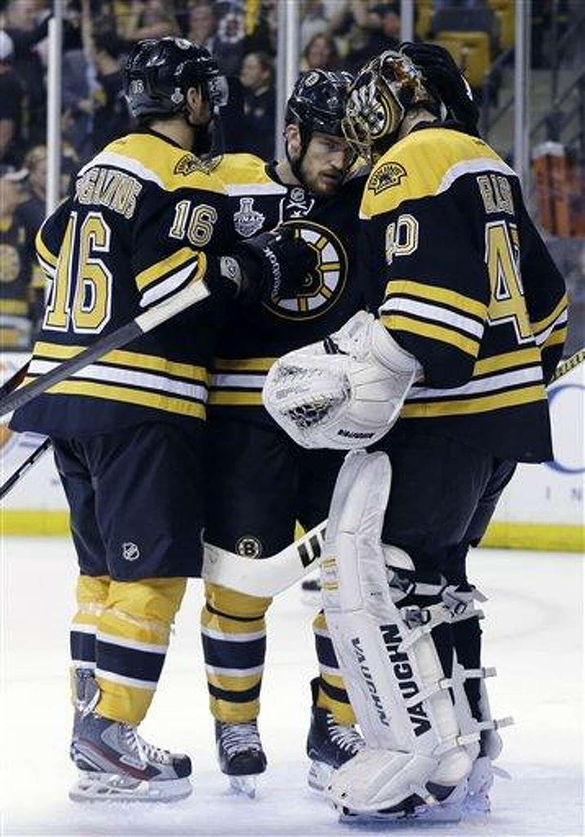 Boston Bruins left wing Kaspars Daugavins (16), of Latavia, and defenseman Andrew Ference, center, congratulate Boston Bruins goalie Tuukka Rask (40), of Finland, after his shutout against the Chicago Blackhawks 2-0 in Game 3 of the NHL hockey Stanley Cup Finals in Boston, Monday, June 17, 2013. (AP Photo/Elise Amendola)