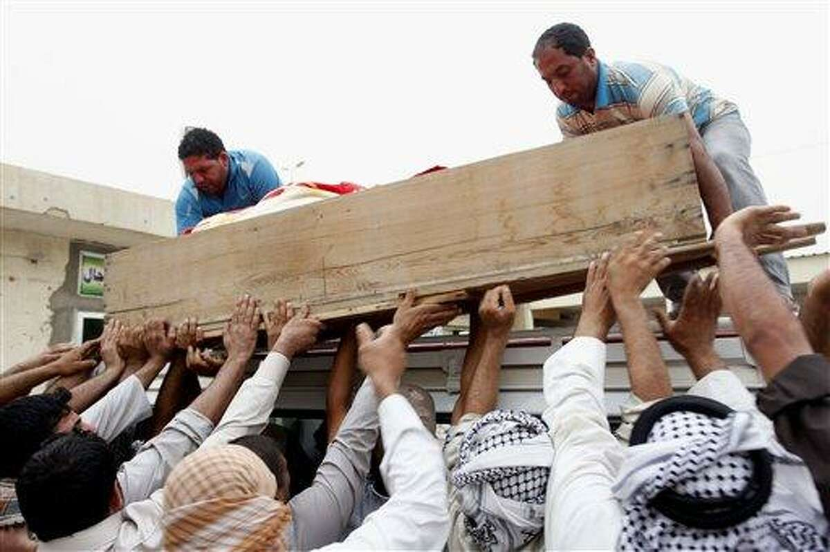 Family members of Ahmed Alwan, 28, who was killed in a car bomb attack, load his coffin onto a vehicle before transporting the coffin for burial in the holy Shiite city of Najaf, 160 kilometers (100 miles) south of Baghdad, Iraq, Monday, May 20, 2013. A wave of car bombings across Baghdad's Shiite neighborhoods and in the southern city of Basra killed and wounded dozens of people, police said. (AP Photo/ Alaa al-Marjani)