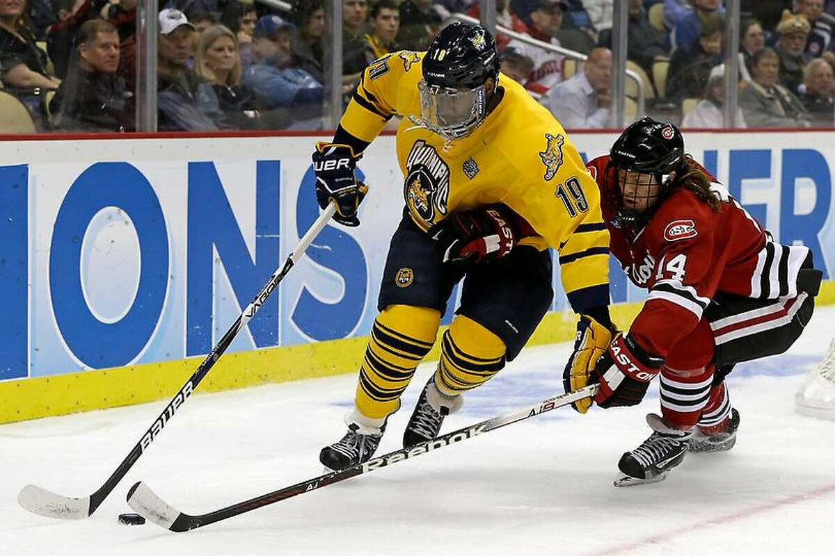 Quinnipiac forward Jordan Samuels-Thomas (19) works the puck in the corner against St. Cloud State's Nick Jensen during the first period of an NCAA college hockey Frozen Four semifinal game in Pittsburgh, Thursday, April 11, 2013. (AP Photo/Gene J. Puskar)