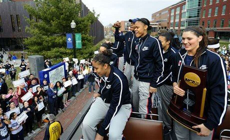 From left, Connecticut's Kaleena Mosqueda-Lewis,Brianna Banks, Moriah Jefferson and Stefanie Dolson sit atop a double-decker bus during a parade through campus honoring the team's win in the women's NCAA Final Four college basketball championship in Storrs, Conn., Wednesday, April 10, 2013. (AP Photo/Jessica Hill) Photo: AP / FR125654 AP