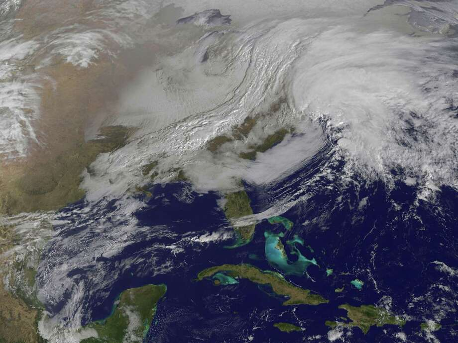 A massive winter storm is coming together as two low pressure systems are merging over the U.S. East Coast. A satellite image from NOAA's GOES-13 satellite on Feb. 8 shows a western frontal system approaching the coastal low pressure area. The satellite image, captured at 9:01 a.m. EST, shows clouds associated with the western frontal system stretching from Canada through the Ohio and Tennessee valleys, into the Gulf of Mexico. The comma-shaped low pressure system located over the Atlantic, east of Virginia, is forecast to merge with the front and create a powerful nor'easter. The National Weather Service expects the merged storm to move northeast and drop between two to three feet of snow in parts of New England