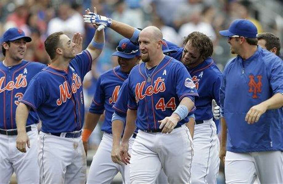 New York Mets pitcher Matt Harvey, far left, watches as David Wright , second from left, celebrates with Kirk Nieuwenhuis, second from right, and John Buck (44) leave the field after Nieuwenhuis hit a ninth-inning, walk-off, three-run, home run off Chicago Cubs relief pitcher Carlos Marmol in a baseball game in New York, Sunday, June 16, 2013. (AP Photo/Kathy Willens) Photo: AP / AP