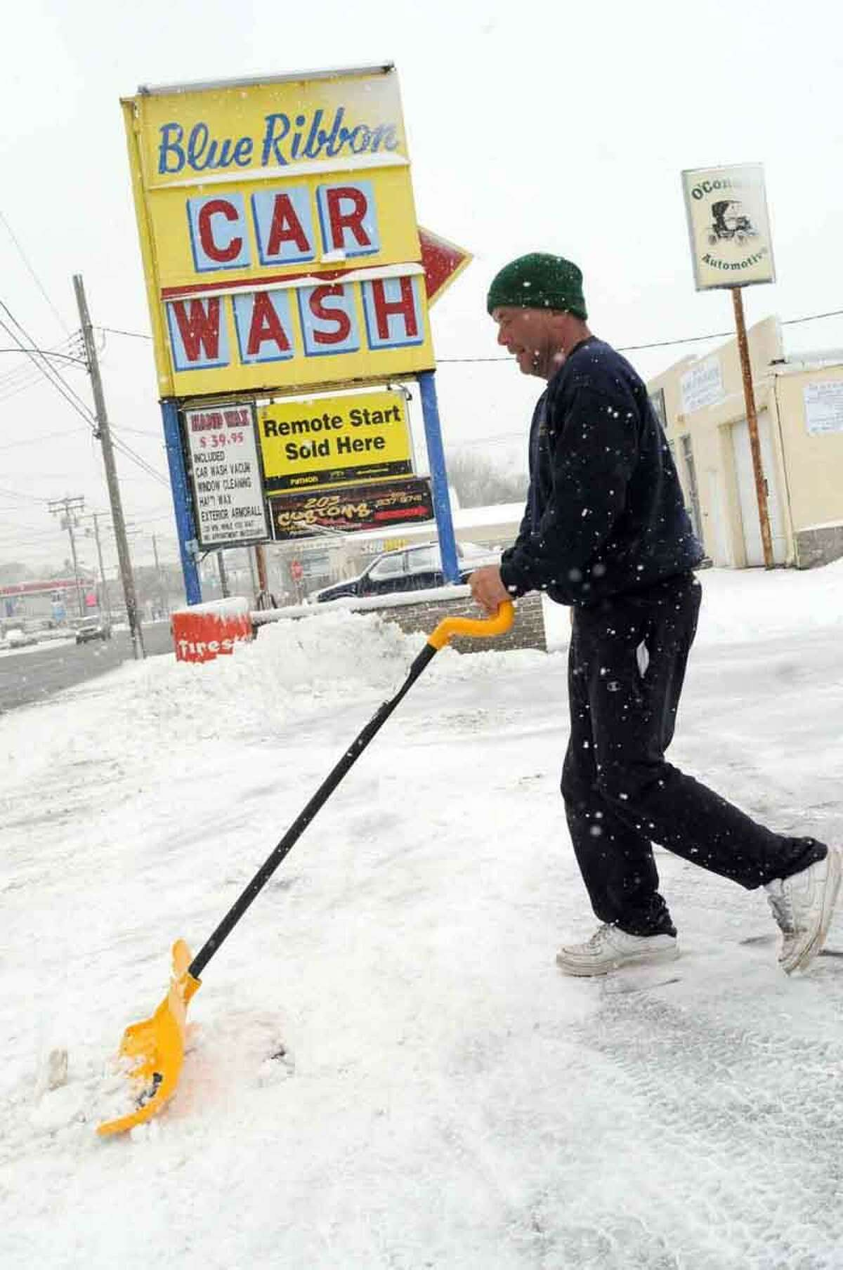 Terry Stone, a Blue Ribbon Car Wash employee, shovels snow from the front of the Elm Street car wash Friday, February 8, 2013 in West Haven. Stone says that once the snow stops the car wash business will be booming. Connecticut.Blizzard warnings have been issued for all of Connecticut, according to the National Weather Service. Connecticut residents should brace for a possible blizzard Friday and into Saturday that could dump up to two feet of snow, along with high winds and the potential for coastal flooding. Friday, February 8, 2013. Photo by Peter Hvizdak / New Haven Register