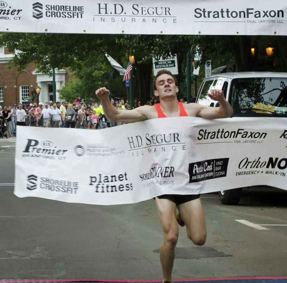Melanie Stengel -- Register    Chris Zablocki, of Essex, crosses the finish line to win the 33rd Annual Branford Road Race on Sunday. The race covers a five mile course.